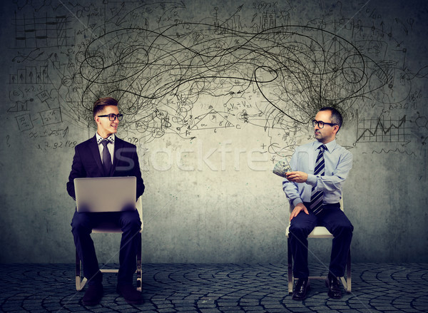 two business men looking at each other one with laptop another offering money for IT service  Stock photo © ichiosea
