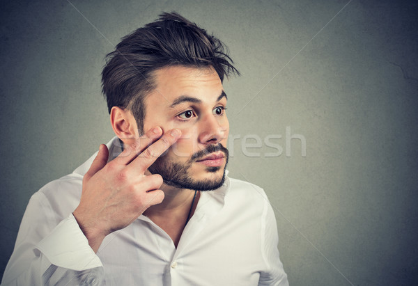 man pulling down eyelid checking his eye looking in mirrow feels unwell Stock photo © ichiosea