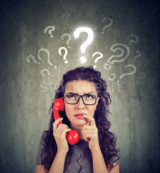 Upset worried confused woman talking on a phone has many questions Stock photo © ichiosea