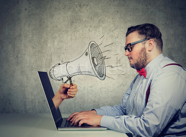 man sitting at table working on computer screaming with a megaphone poking out from a laptop screen Stock photo © ichiosea