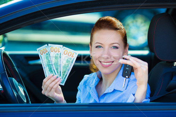 Woman holding car keys, dollar bills, sitting in her new car Stock photo © ichiosea