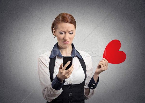 displeased woman reading news on phone throwing away heart Stock photo © ichiosea
