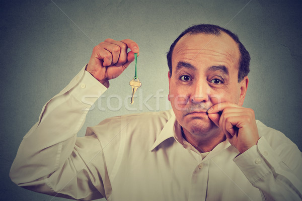 Stock photo: Man with mouth shut holding a key isolated on gray wall background