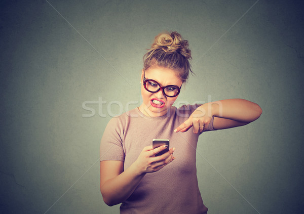 Stock photo: Angry young woman screaming on mobile phone. Negative human emotion