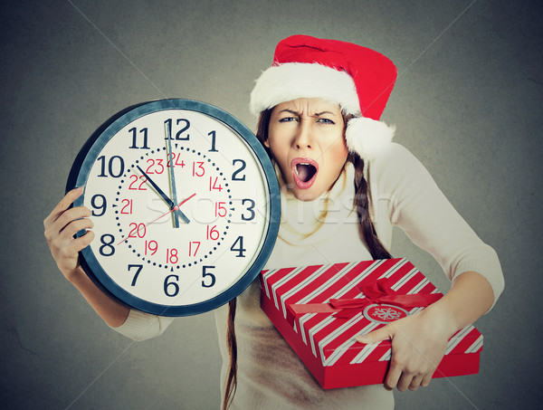 stressed in a hurry woman wearing santa claus hat holding clock gift box Stock photo © ichiosea