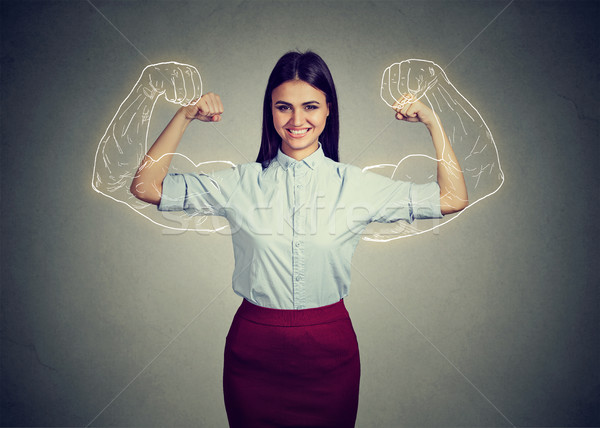 Powerful confident woman flexing her muscles. Stock photo © ichiosea