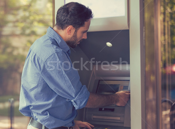 Young man using ATM outdoors  Stock photo © ichiosea