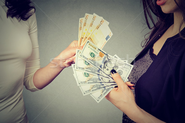 Women holding money exchanging with each other dollars to euro cash  Stock photo © ichiosea