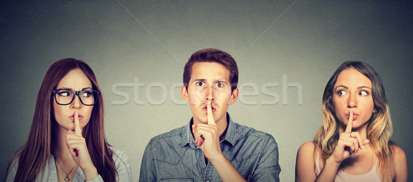 Secretive young people man and two women with finger to lips gesture   Stock photo © ichiosea