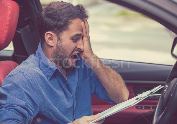 Stressed desperate man driver with papers sitting inside his car  Stock photo © ichiosea