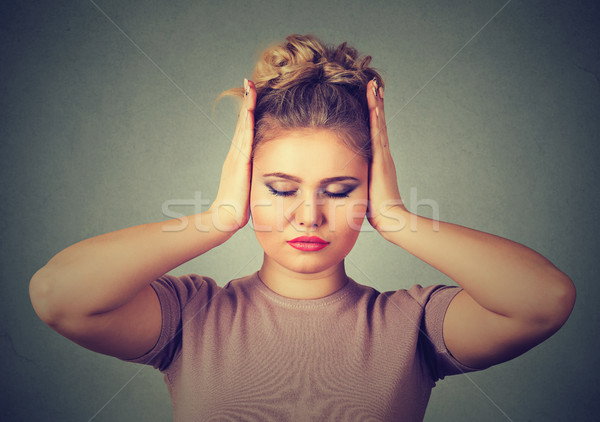 Too loud sound. Beautiful young woman covering ears with hands and keeping eyes closed  Stock photo © ichiosea
