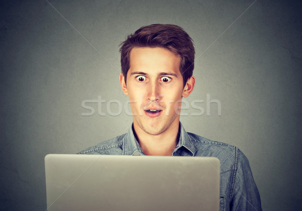 Shocked man looking at laptop  Stock photo © ichiosea