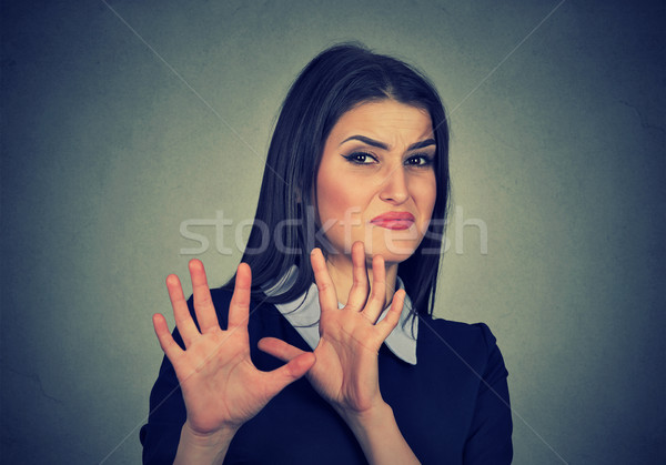 Young woman with disgusted expression dodging something Stock photo © ichiosea
