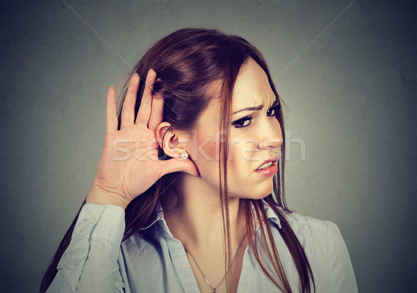 Stock photo: Woman with hand to ear gesture listening carefully