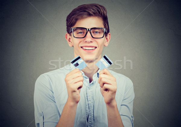 Happy debt free student holding a credit card cut in two pieces Stock photo © ichiosea