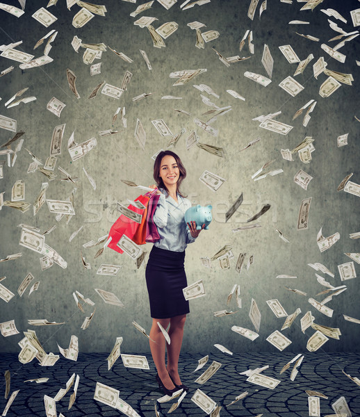 Happy woman with shopping bags and piggy bank standing under money rain Stock photo © ichiosea
