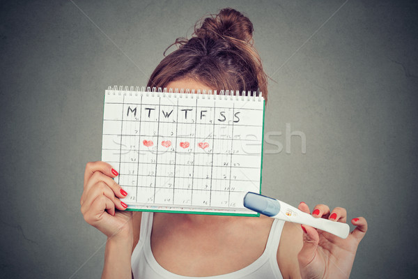 woman hiding behind a periods calendar and showing a positive pregnancy test  Stock photo © ichiosea