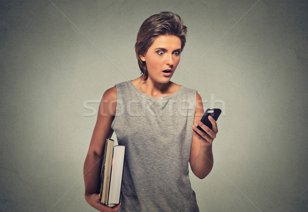 nxious looking young woman starring at cell phone seeing bad news or photos Stock photo © ichiosea