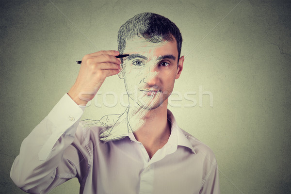 Young man drawing self portrait face, hiding true emotion. Private life, identity concept.  Stock photo © ichiosea