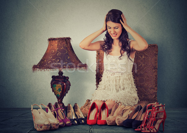 Stressed woman making decisions picking up the right pair of high heel shoes Stock photo © ichiosea