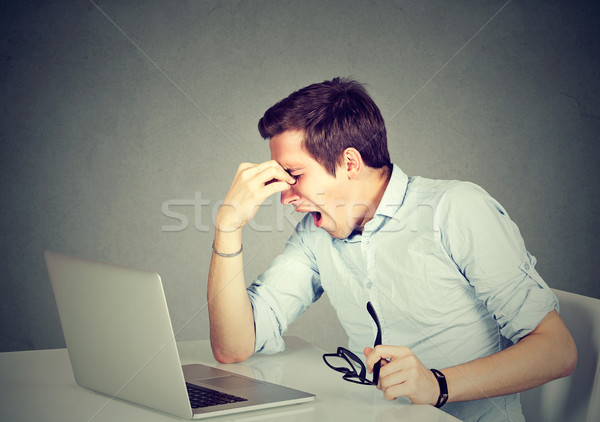 Tired man massaging his closed eyes sitting in front of laptop  Stock photo © ichiosea