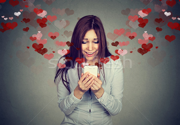 young woman receiving love sms text message on mobile phone  Stock photo © ichiosea