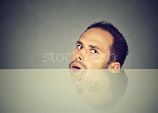 Gyanús ijedt fiatalember asztal rejtőzködik arc Stock fotó © ichiosea