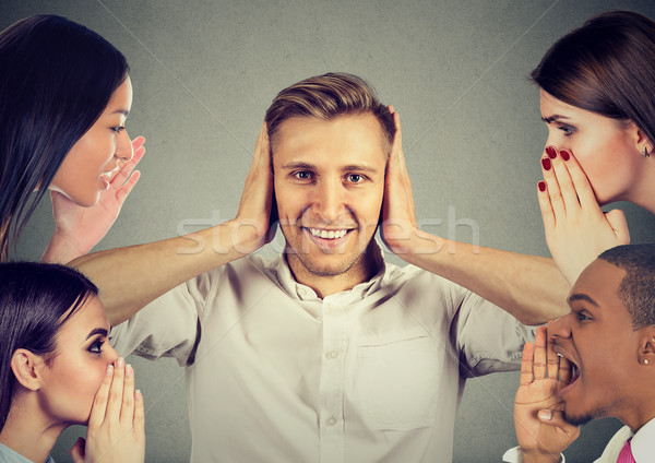 people whispering a secret gossip to a man who covers ears ignoring them  Stock photo © ichiosea