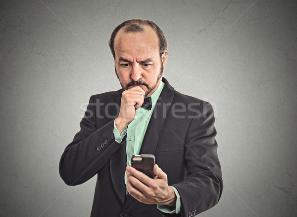 confused business man looking on smartphone thinking what to reply Stock photo © ichiosea
