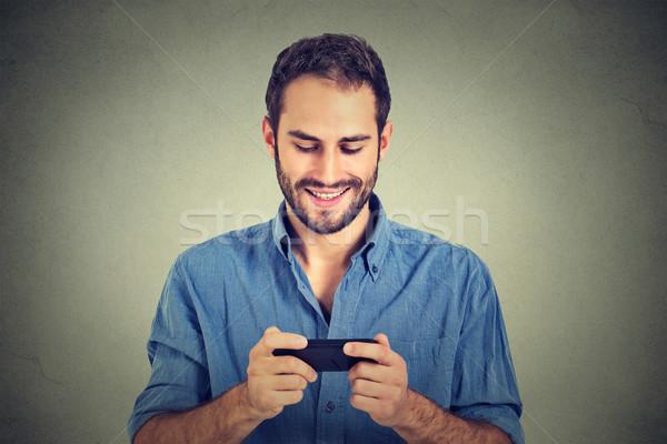 Mosolyog férfi néz okostelefon sms üzenetküldés néz Stock fotó © ichiosea