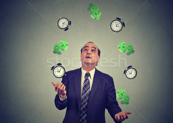 business man juggling throwing up alarm clocks dollar signs. Time is money concept Stock photo © ichiosea