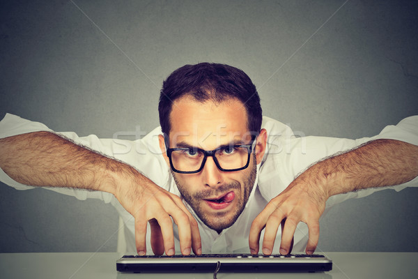 Crazy looking nerdy man typing on the keyboard Stock photo © ichiosea