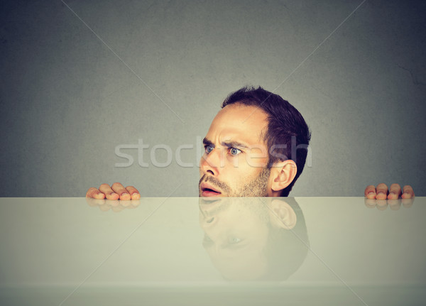 suspicious man peeking from under the table Stock photo © ichiosea