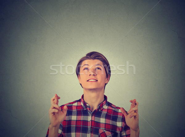 Young guy, man crossing fingers, wishing looking up Stock photo © ichiosea