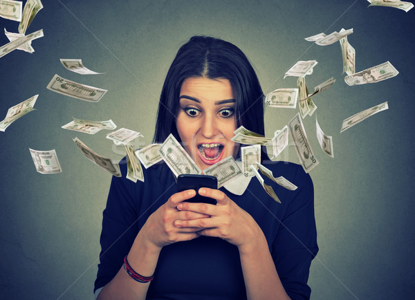 Surprised woman using smartphone dollar bills flying away from screen  Stock photo © ichiosea