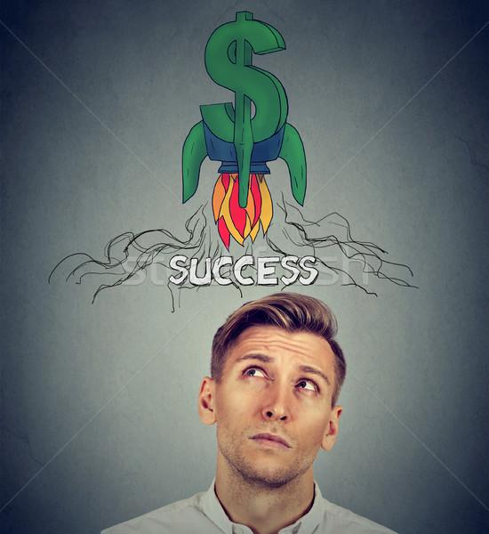 Nadenkend jonge man raket dollarteken boven Stockfoto © ichiosea