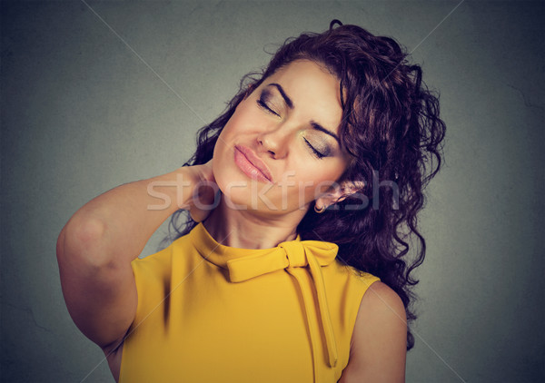 Back and spine disease. Woman massaging painful neck  Stock photo © ichiosea