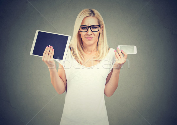 Perplexed young woman in glasses shrugging shoulders uncertain what to choose tablet or smartphone  Stock photo © ichiosea