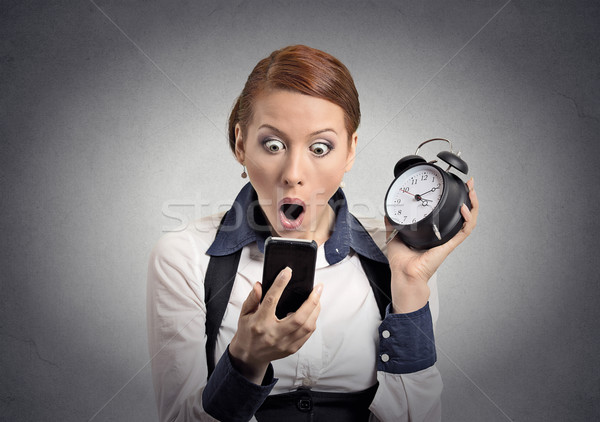 shocked business woman with alarm clock looking at smart phone Stock photo © ichiosea