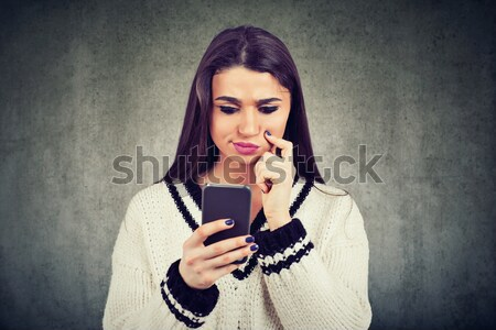 Woman with headphones reading sms on smartphone listening radio Stock photo © ichiosea