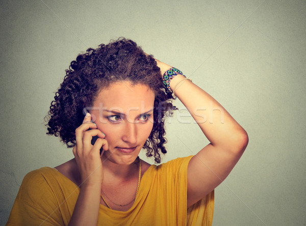 unhappy young woman talking on mobile phone looking down stressed  Stock photo © ichiosea