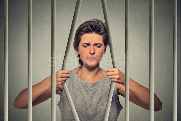 Stressed desperate sad woman bending bars of her prison cell Stock photo © ichiosea