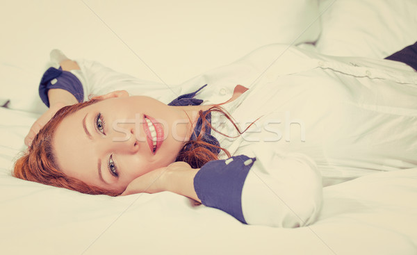 Businesswoman with hands behind head lying in bed hotel room Stock photo © ichiosea