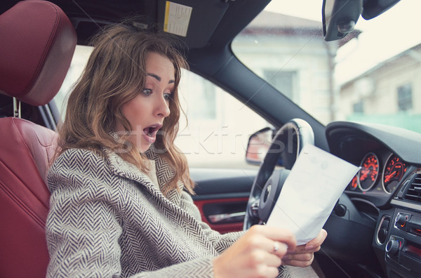 Shocked woman in car reading insurance paper Stock photo © ichiosea