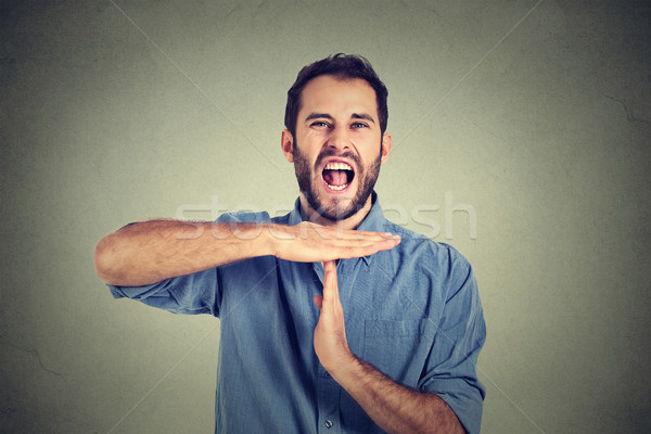 Young man showing time out hand gesture, frustrated screaming to stop Stock photo © ichiosea