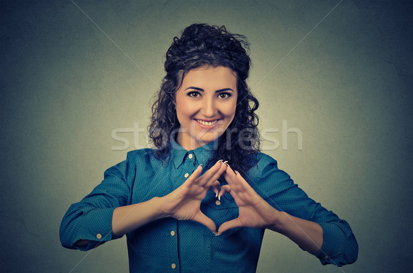 smiling cheerful happy young woman making heart sign with hands Stock photo © ichiosea