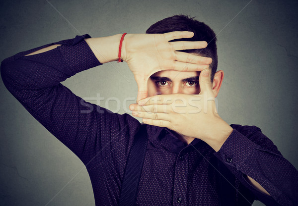 Young man peeking through his fingers hands  Stock photo © ichiosea