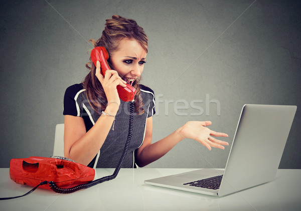 Angry young woman calling customer service with a laptop failure Stock photo © ichiosea