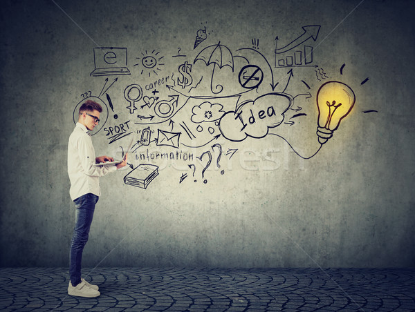 Man using a laptop with light bulb plugged in it and info graphic plan written on concrete wall  Stock photo © ichiosea
