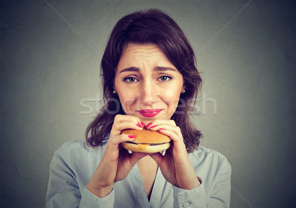 Woman with guilty feeling to eat a hamburger  Stock photo © ichiosea